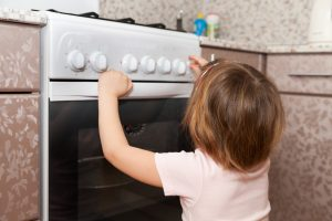 Child playing with stove knobs